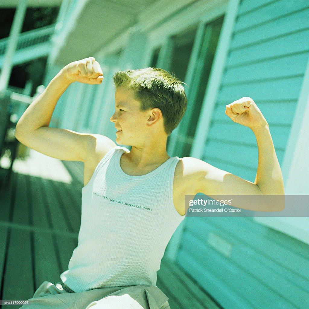 Teenage boy flexing arm muscles : Stockfoto