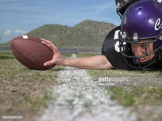 teenage boy (16-18) football player on field, touching ball - touchdown stock-fotos und bilder