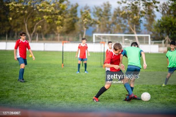 teenage boy fußballer im training spiel konkurrieren - jugendmannschaft stock-fotos und bilder