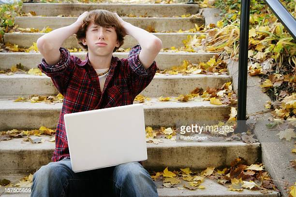 Teenage Boy Frustrated While Using Computer in Nature