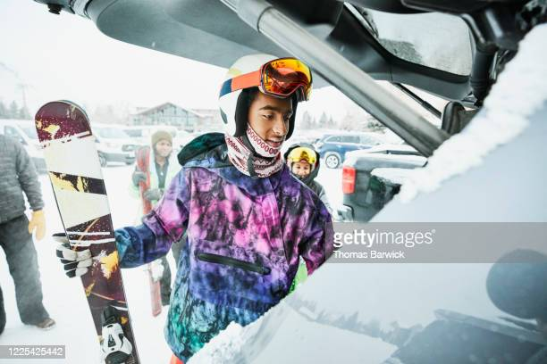 teenage boy getting gear out of car before skiing with family - winter sport stock pictures, royalty-free photos & images