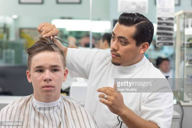 Teenage boy getting hair styled