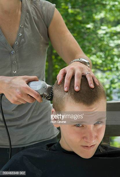Teenage boy (14-16) getting haircut by woman, portrait