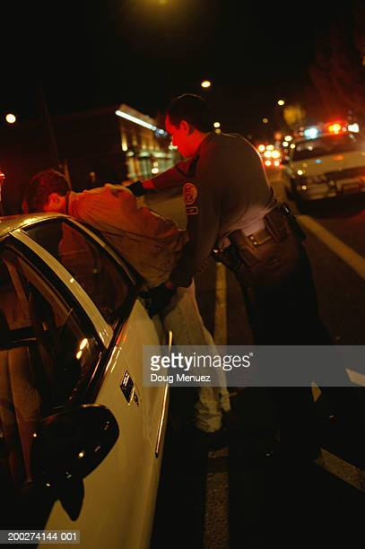 Teenage boy (16-17) getting handcuffed, side view