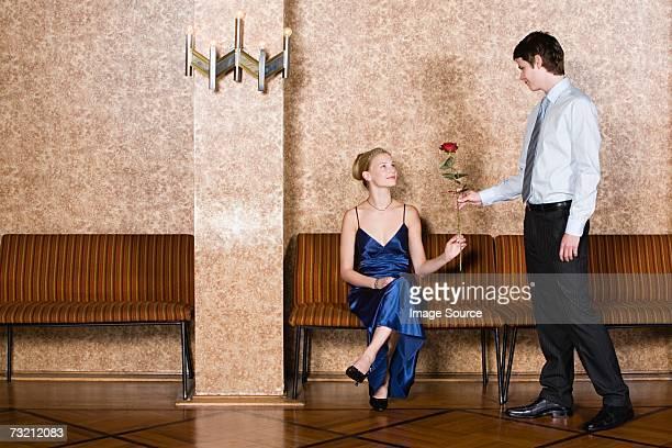 Teenage boy giving teenage girl rose