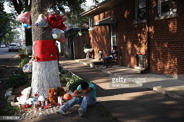 A teenage boy grieves next to a makeshift memorial at the site where Ashley Hardmon was shot and killed on July 4 2013 in Chicago Illinois Hardmon...