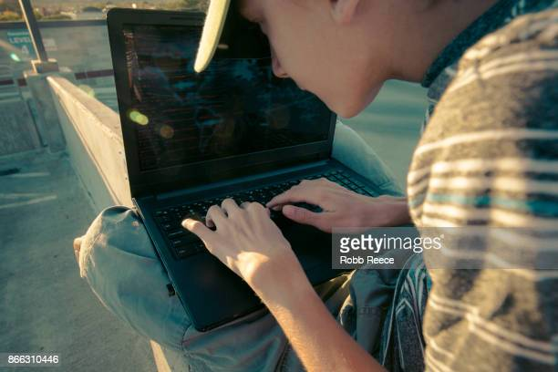 A teenage boy hacking with a laptop computer to commit cyber crime