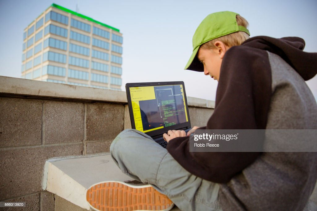 A teenage boy hacking with a laptop computer to commit cyber crime : Stock Photo
