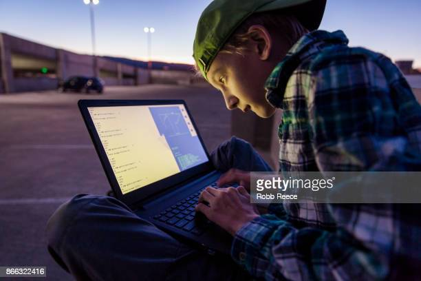 a teenage boy hacking with a laptop computer to commit cyber crime - robb reece stock-fotos und bilder