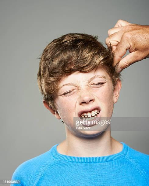 teenage boy having hair pulled