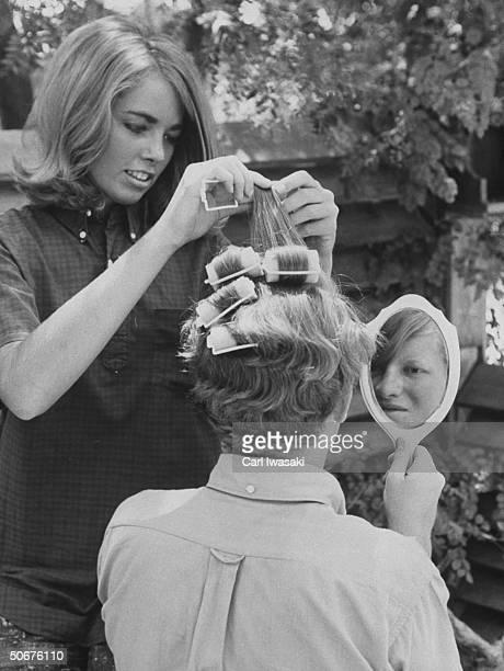 Teenage boy having hair set in curlers by girl
