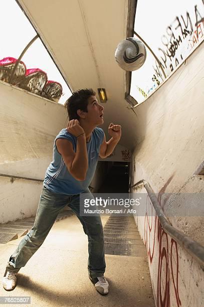Teenage boy heading ball in underpass