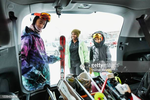 teenage boy helping family get gear out of car before going skiing - recreational pursuit stock pictures, royalty-free photos & images