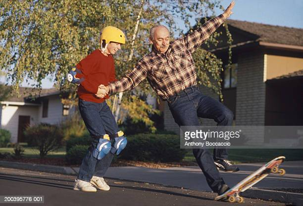 Teenage boy (13-15) helping grandfather skateboard