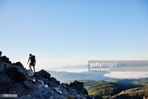 teenage boy hiking up rocky ridgeline - moving up stock pictures, royalty-free photos & images