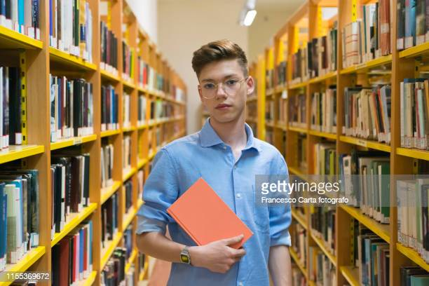 teenage boy hold a book in the library - man holding book stock pictures, royalty-free photos & images