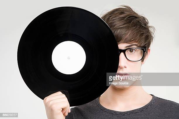 A teenage boy holding a vinyl record