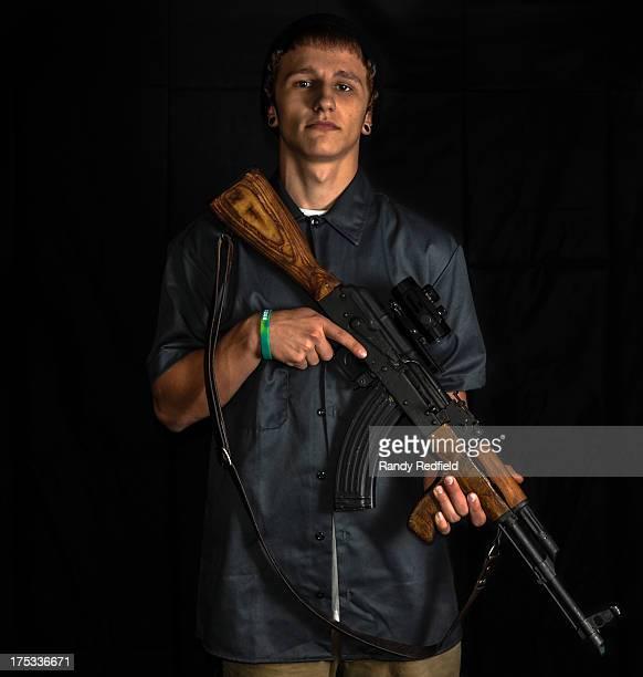 Teenage boy holding an AK47 assault rifle. Studio shot on a black background.