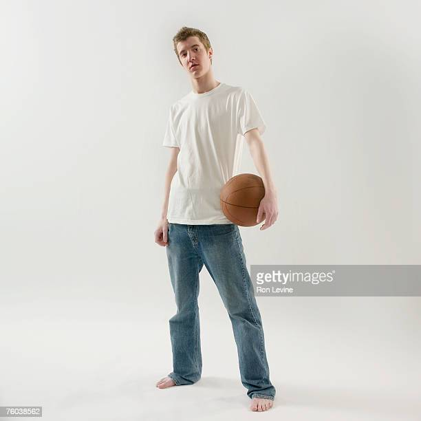 Teenage boy (16-17) holding basketball, portrait