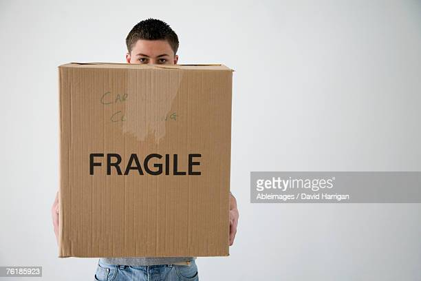 Teenage boy holding cardboard box