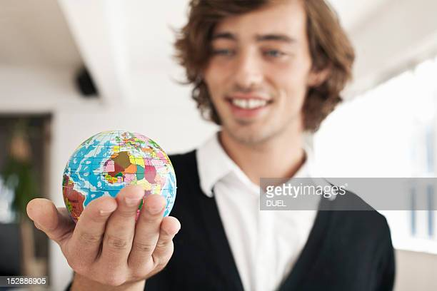 Teenage boy holding miniature globe
