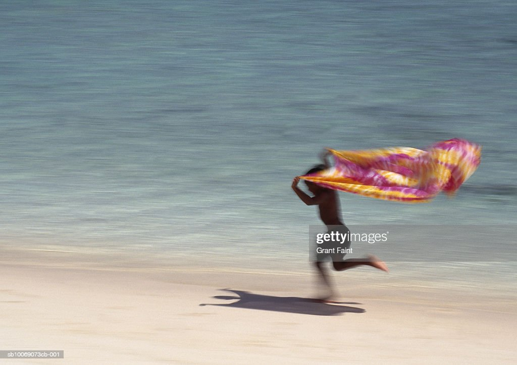 Teenage boy (14-15) holding sarong over head, running on beach, blurred motion : Stockfoto