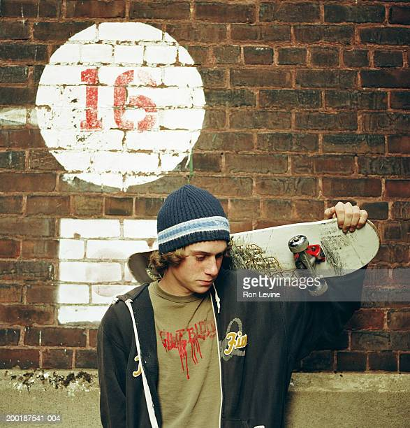 Teenage boy (16-18) holding skateboard in front of brick wall