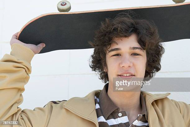 Teenage Boy Holding Skateboard