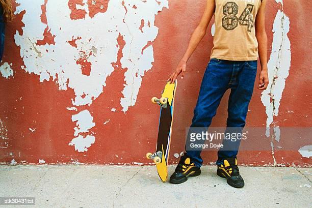 Teenage boy holding skateboard (low section)