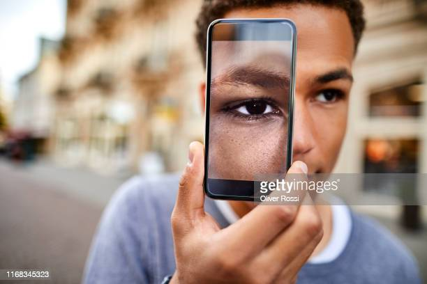teenage boy holding smartphone showing his eye - 16 17 ans photos et images de collection