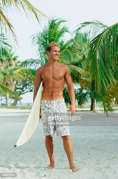 Teenage boy (16-18) holding surfboard on beach
