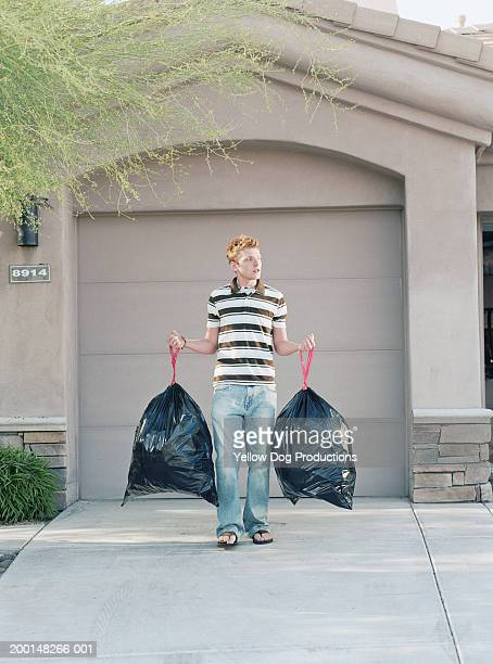 Teenage boy (16-18) holding two large garbage bags in driveway