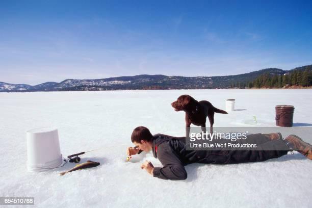 Teenage Boy Ice Fishing with his Dog