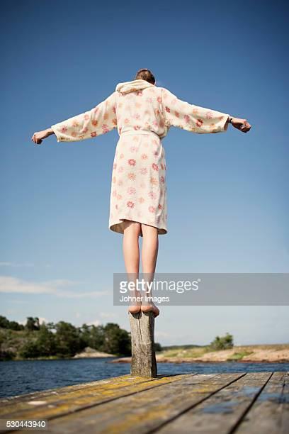 Teenage boy in bathrobe balancing on jetty