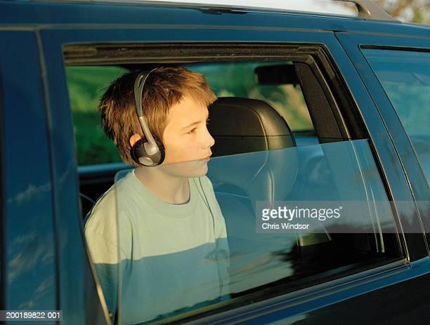 Teenage boy (13-15) in car looking out window, wearing headphones