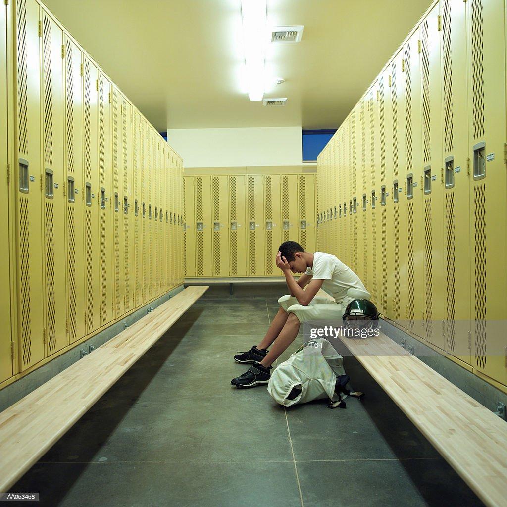 Teenage boy (15-17) in football uniform, sitting in locker room : Foto de stock
