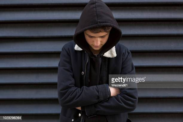 teenage boy in front of black background wearing hooded jacket - hooded shirt stock pictures, royalty-free photos & images