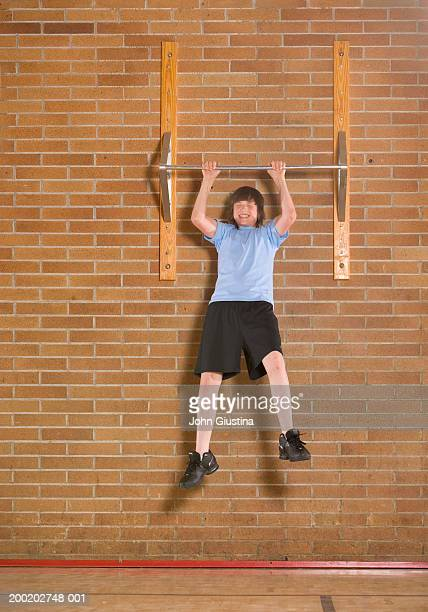 Teenage boy (13-14) in gym doing pull ups