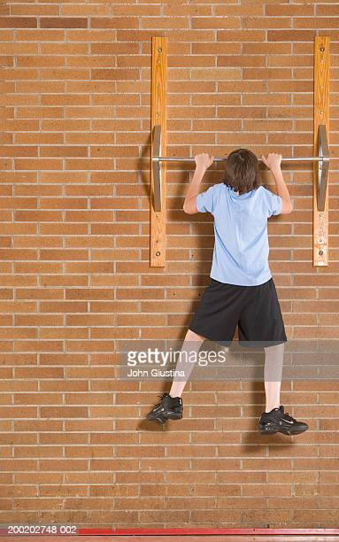 Teenage boy (13-14) in gym doing pull ups, rear view