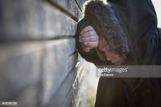 Teenage boy in hooded coat, leaning against a wall in despair
