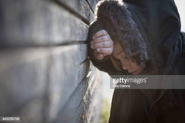 Teenage boy in hooded coat, leaning against a wall in despair