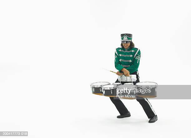Teenage boy (16-18) in marching band uniform playing drums, smiling