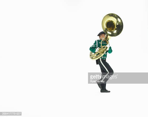Teenage boy (16-18) in marching band uniform playing tuba, side view