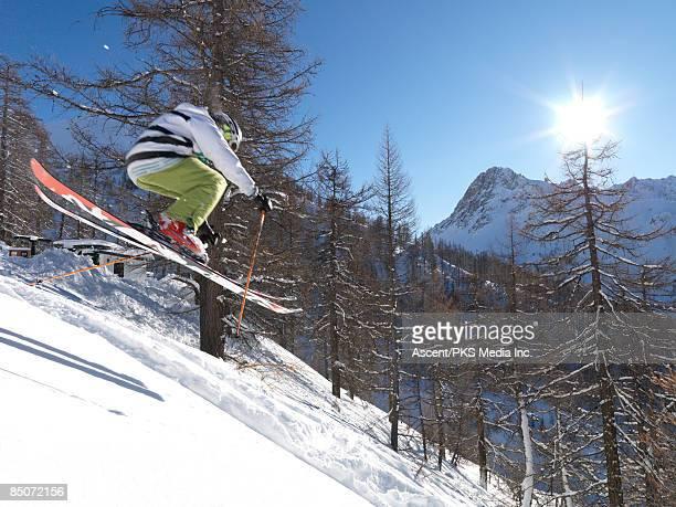 Teenage boy in mid-sir ski descent, in forest