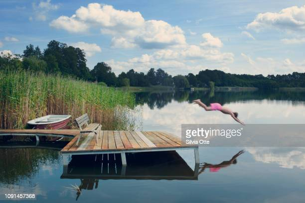 Teenage boy in pink swim trunks diving into lake from jetty with blue skies in background