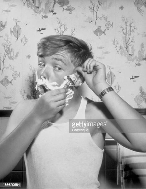 Teenage boy in sleeveless tshirt shaving with shaving cream and blade June 12 1964