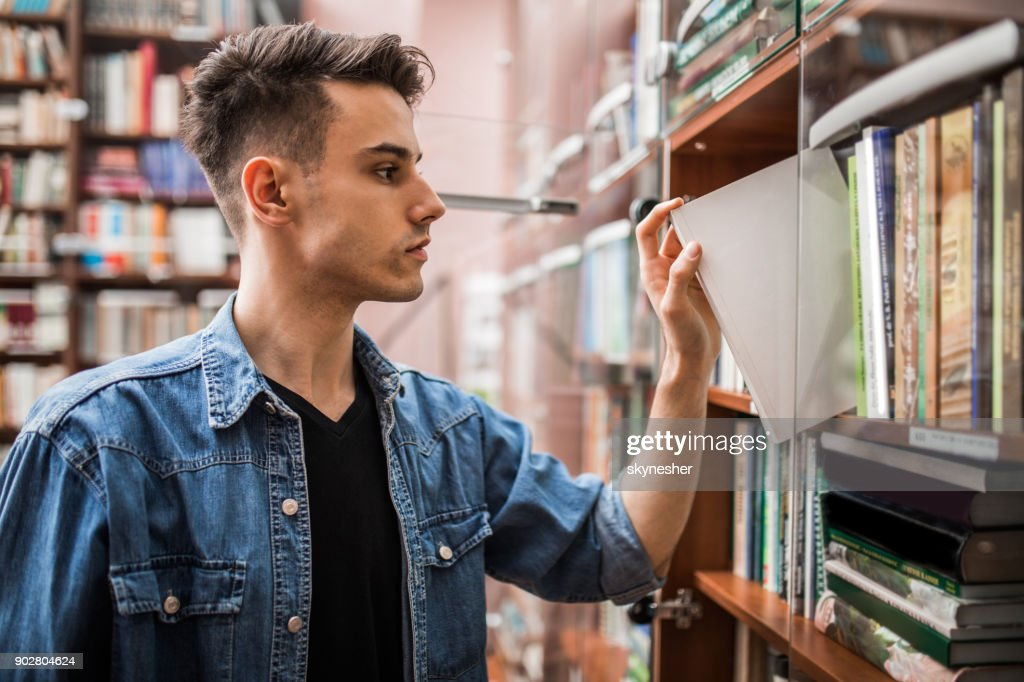 Teenage boy in the library choosing book from the bookshelf. : Stock Photo