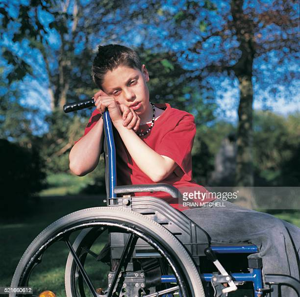 Teenage boy in wheelchair looking sad