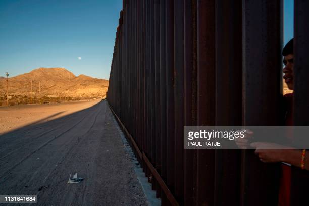 A teenage boy is pictured peering through the metal fencing on the USMexico border in Anapra New Mexico on March 19 2019 Speaking of an 'invasion' of...