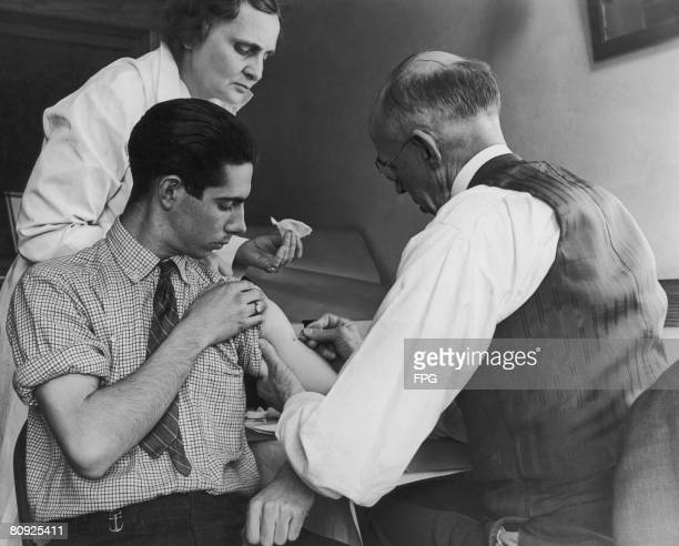 Teenage boy is vaccinated against smallpox by a school doctor and a county health nurse, Gasport, New York, 15th March 1938.